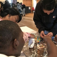 Three participants are decorating ginger bread houses.  ID: Participants are leaning over a table.