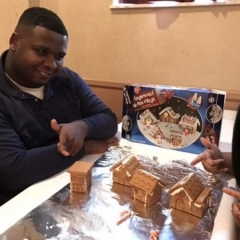 Participant smiles and points at ginger bread houses he has helped make.  ID:  The participant is wearing a dark sweatshirt.