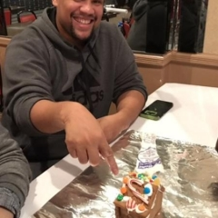 Participant is pointing to a ginger bread house he has helped make.  ID: Participant is wearing a gray sweatshirt.