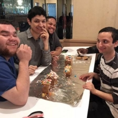 Participants smile for the camera.  ID:  Participants sit around a table with ginger bread houses that they have made.