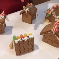 Ginger bread houses made by Day Habilitation participants.  ID:  Ginger bread houses on a white cloth.