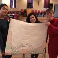 "Participants hold up a table cloth that they made themselves.  ID:  The cloth reads ""Home Sweet Home""."