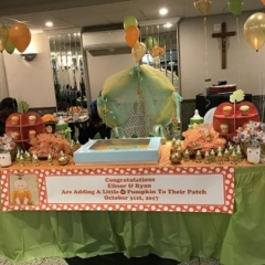 A table with a Halloween display.  ID: The table is decorated with  balloons and Halloween inspired deserts.