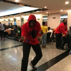 A participant poses as Spider Man.  ID: A participant is wearing a red sweatshirt with a picture of a spider on it.