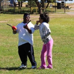 Participants playing with a nerf football.  ID: Two participants standing in a field while one of them hold two nerf footballs.