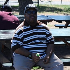 A participant enjoying a quite moment in the shade.  ID: A participant wearing a striped shirt is sitting on a bench.