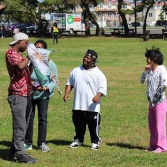 Participants playing with a kite.  ID:  One participant is holding up a kite while another three observe.