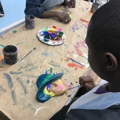 A participant paints a figure made out of clay.