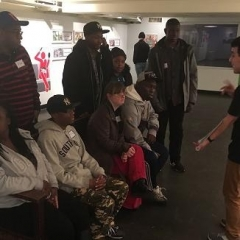 The group listens to the guide at the Transit Museum.