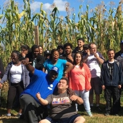 Participants at Decker Farms.  ID: A group of participants standing in a corn field.