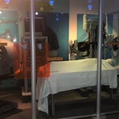 A robotics display at the Liberty Science Center.  ID: A representation of a hospital room with various robotics to handle patient care.