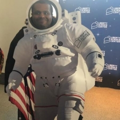 Participant at a Liberty Science Museum.  ID: A participant is wearing a space flight suite.
