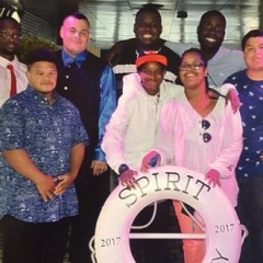 "A group of participants smile for a group picture.  ID: Participants stand on board of a cruise in front of a life saver that reads ""Spirit New Jersey 2017""."