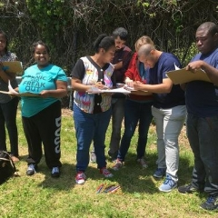 Participants at an Art Therapy class.  ID: A group stands in the park and are writing notes on paper.