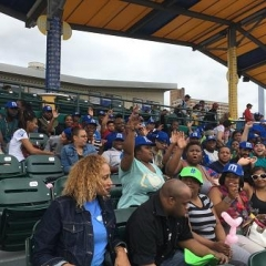 Participants cheer at the Brooklyn Cyclones game.  ID: Participants are sitting in the stands.
