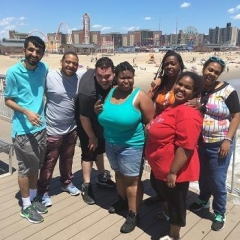 Participants pose for a picture on Coney Island.  ID: Participants are standing on a wooden boardwalk.  Behind them is Coney Island beach and Luna Park rides.