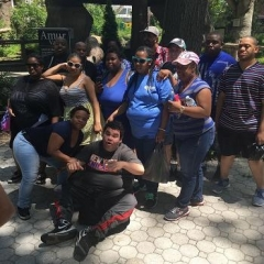 Participants pause at the zoo to take a picture.  ID: The group gathers to take a photo.