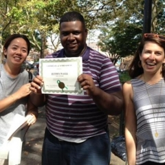 Day Habilitation participant holds up an award he received for participating in Therapeutic Garden Project for People of All Abilities.  ID: The participant is wearing a purple and white striped shirt.