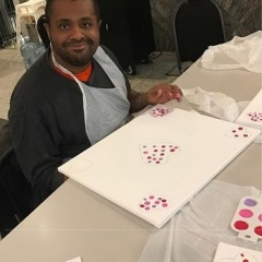 Participant finger painting a Valentine's day inspired artwork.