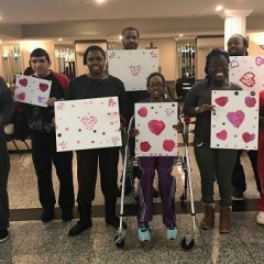 Participants hold up their Valentine's Day artwork.