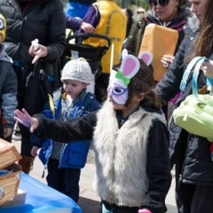 A girl reaching for the treasure chest.  ID: The girl is wearing Easter Bunny mask.