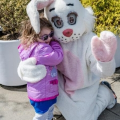A girl is hugging Easter Bunny.  ID: A white Easter Bunny is hugging a little girl wearing a pink jacket.