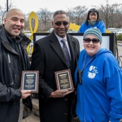 ATF agents receive an award for their help with the Beeping Eggs.  ID:  Two ATF agents stand with Holly Bonner, the Director of Accessibility for City Access New York.