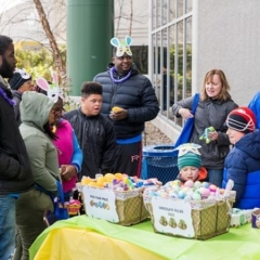 Kids wait for the Egg Hunt to begin.  ID: Egg Hunt participants stand by a table with Easter Egg baskets on it.