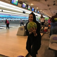 Ilene Rosen, the event organizer, is getting ready to bowl.  ID: Ilene is holding up a green bowling ball.