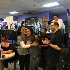 Attendees hug and clap to celebrate a strike.  ID: Four attendees smiling.
