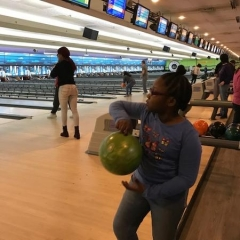 A participant prepairing to bowl.  ID: A participant is holding a green bowling ball.