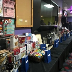 Raffle display.  ID: Raffle Table featuring various baskets prizes on a black tablecloth.
