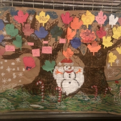 A mural made by City Access Participants.  ID: Colorful leafs with a snowman in the center.