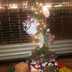 A Christmas Tree made by City Access participants out of recyclable materials.  ID:  The tree is covered by colorful ornaments.