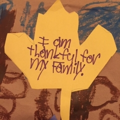 """A yellow paper leaf handwritten by City Access participant as part of a larger mural.  ID: The leaf reads:  I am thankful for my family."""""""