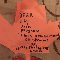 An orange paper leaf handwritten by City Access participant as part of a larger mural.  ID: The leaf reads: Dear City Access Program.  Thank you so much for special day.""