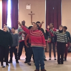 Participants dance during a performance for the winter holiday party.  ID: Participants in striped sweaters wave as part of the dance performance.