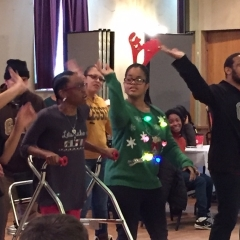 Participants perform a dance during the holiday party celebration.  ID: Participant is wearing a green sweater with colorful ornaments on it.