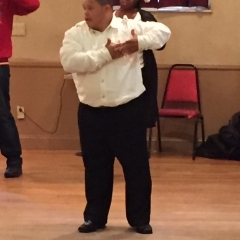 A participant during a dance performance.  ID: Participant is wearing a white shirt.