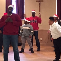 Participants perform a dance.  ID: Wearing red and white Santa hats, participants perform a dance.