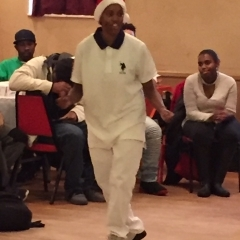 A participant in the middle of a dance.  ID: Participant dressed in all white.