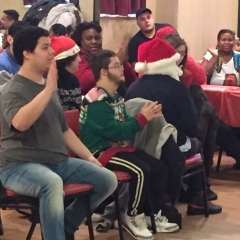Participants in the audience clap for those that just performed.  ID:  Participants sitting around and watching the performance.