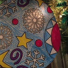 A colorful paper ornament made by City Access participants.  ID: Ornament with a yellow stars and white snowflakes.