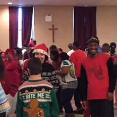 Participants mingle and dance after the performance.  ID: Participants dressed in holiday themed colors.