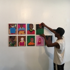 A participant is putting up a display of self portraits at  The Living Gallery in Brooklyn.