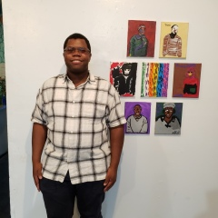 A participant poses next to a display of self portraits.