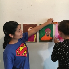 Participants are putting up a display of self portraits at  The Living Gallery in Brooklyn.