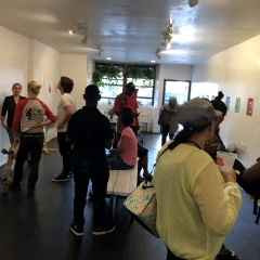 Visitors mingle at The Living Gallery while viewing self portraits of the City Access New York participants.