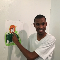 A participant poses next to his self portrait.
