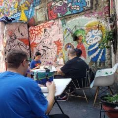 Participants enjoy refreshments in the colorful yard of The Living Gallery.